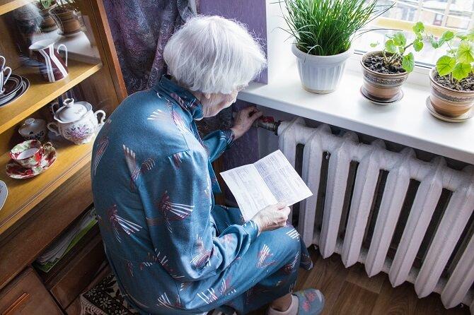 starší paní u topení kouká na účet za plyn