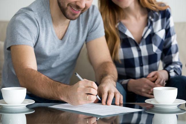 Mladý pár podepisuje smlouvu s novým dodavatelem.