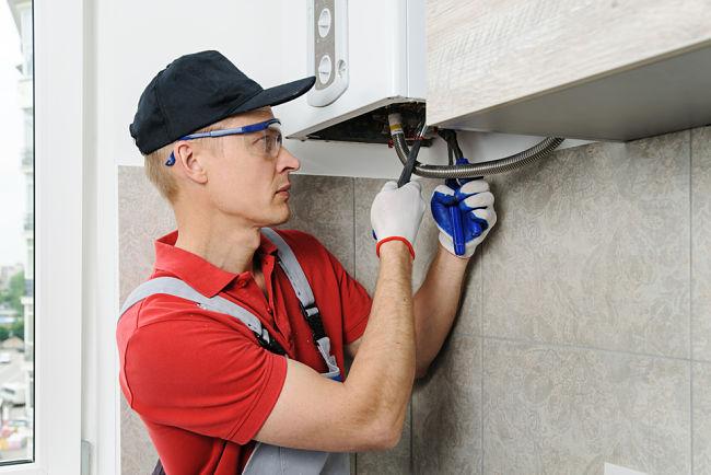 Muž provádí kontrolu plynového kotle.