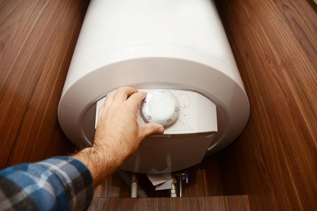 Muž nastavuje kondenzační kotel.