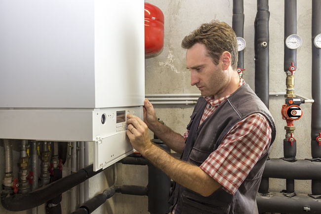 Muž opravuje plynový kondenzační kotel.